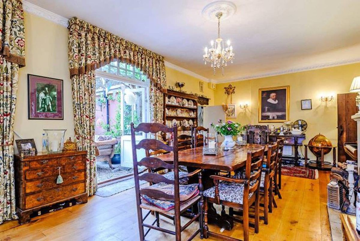 Ornate dining room with formal table and curtains.