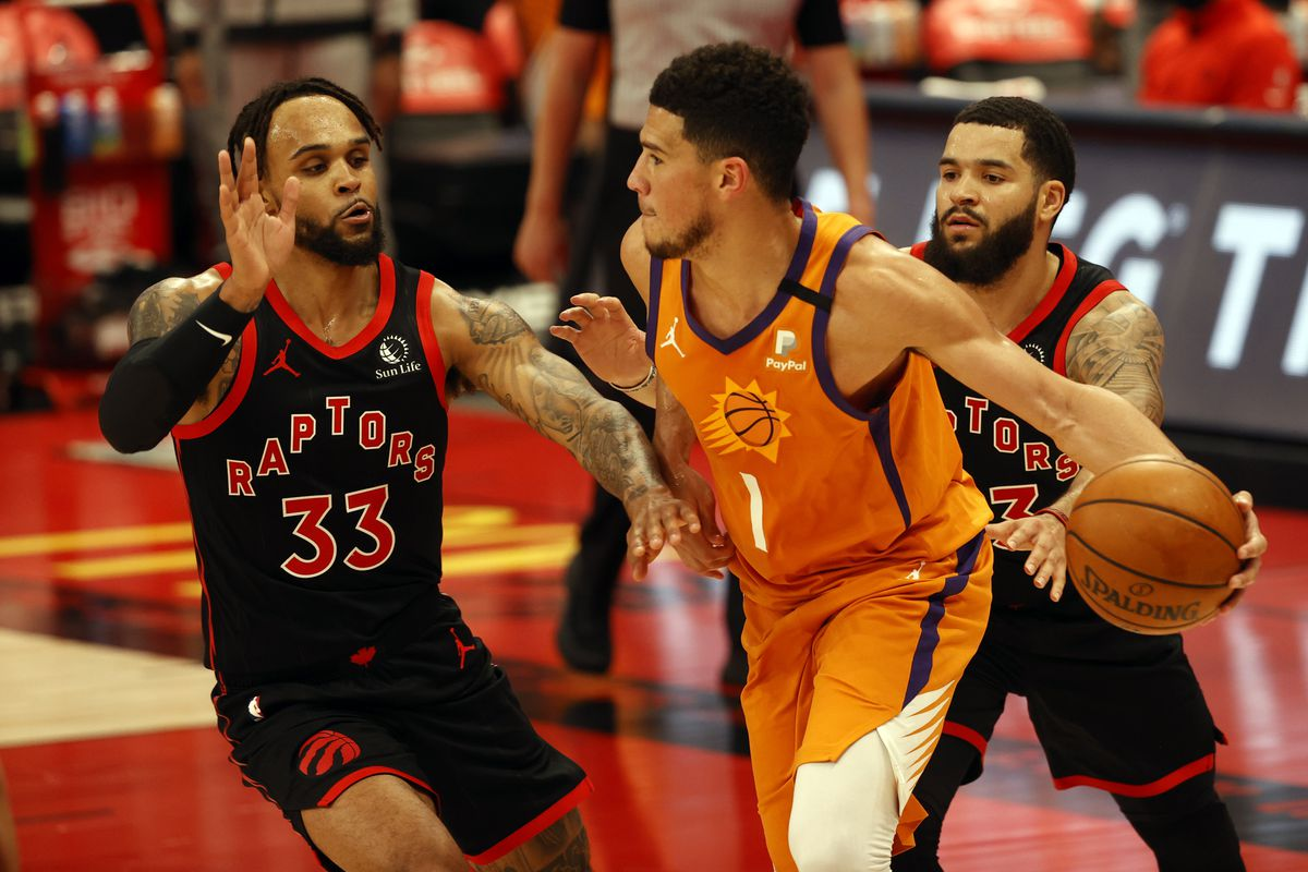 Phoenix Suns guard Devin Booker handles the ball as Toronto Raptors guard Fred VanVleet  and guard Gary Trent Jr. defend during the second half at Amalie Arena
