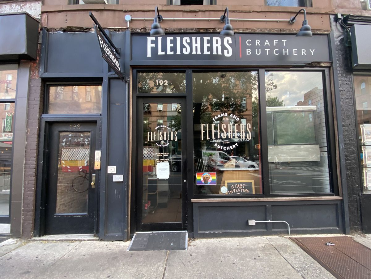 """A dark-colored storefront with glass windows. A logo with the words """"Fleishers Craft Butchery"""" appears on the storefront and on its windows."""