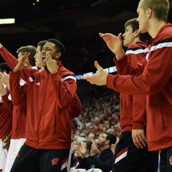 The Badger bench reacts to a made three point shot