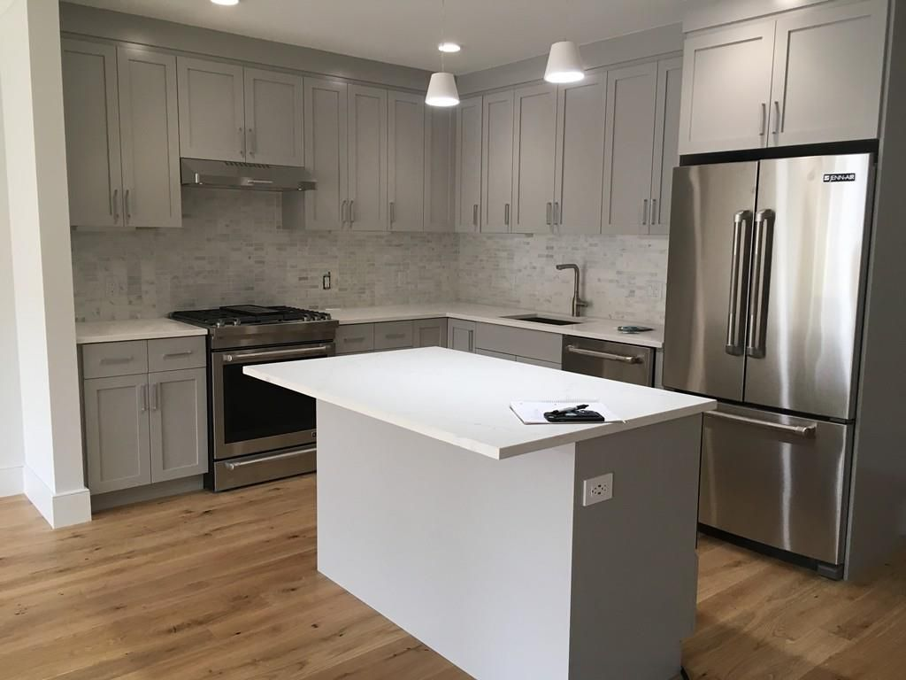 A new modern kitchen with cabinetry and an island.