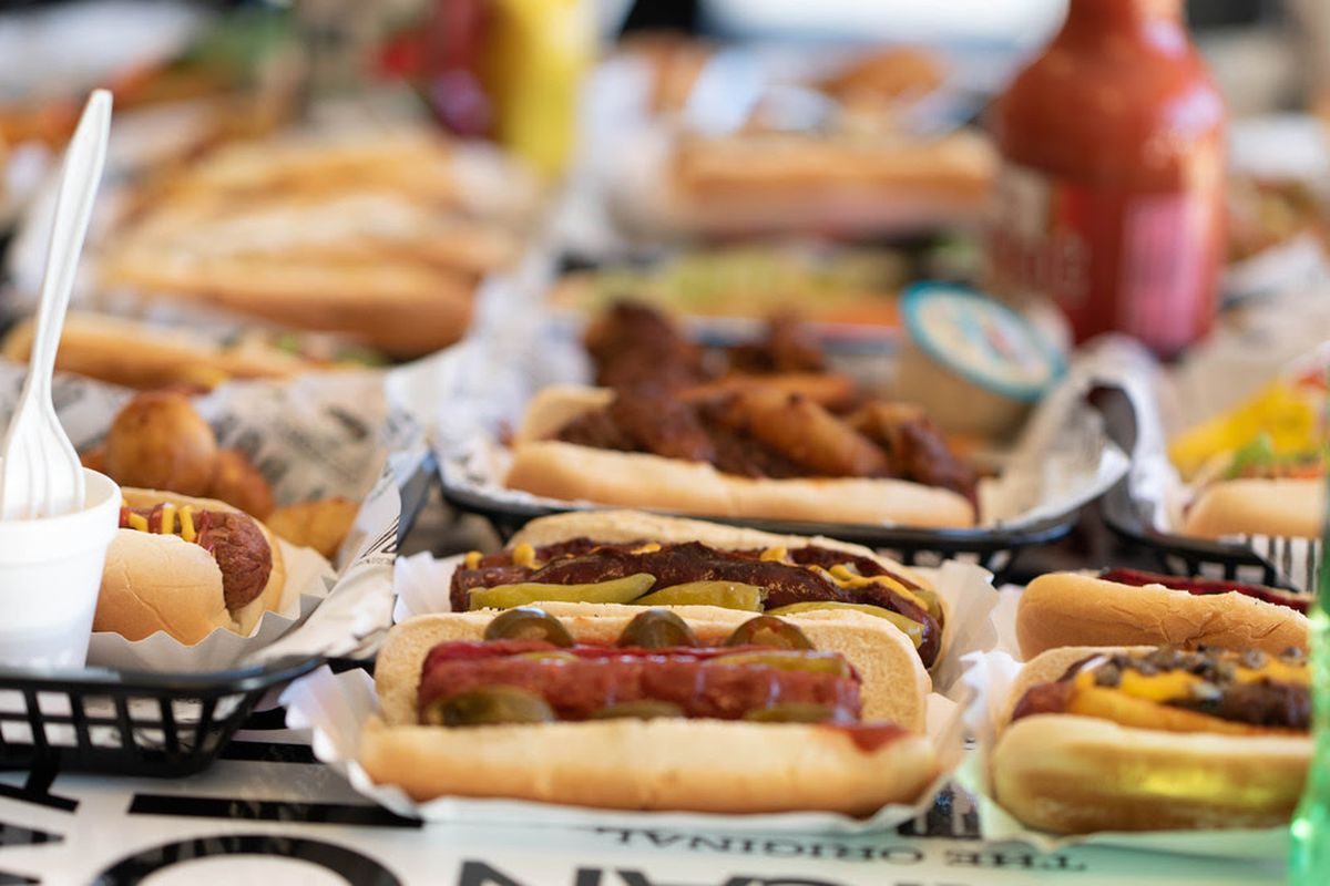 several hot dogs on buns in plastic serving baskets