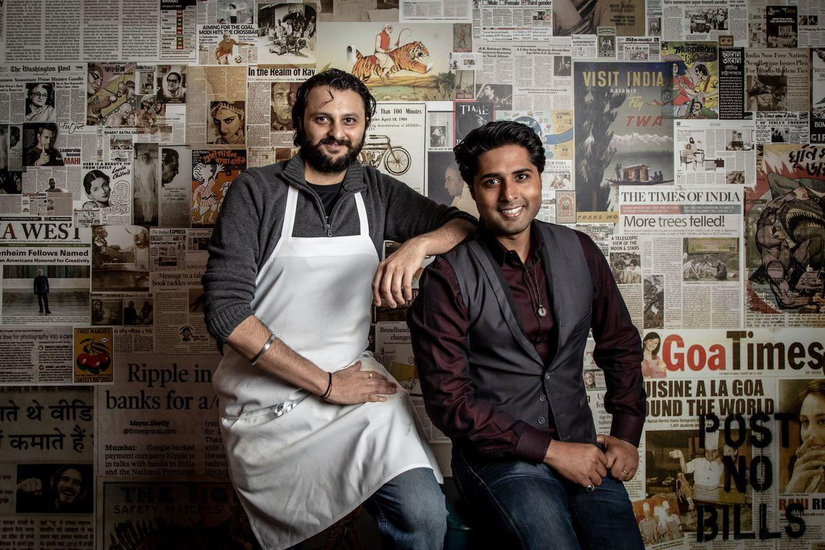 Chintan Pandya and Roni Mazumdar pose in front of a newspapered wall at Long Island City's Adda