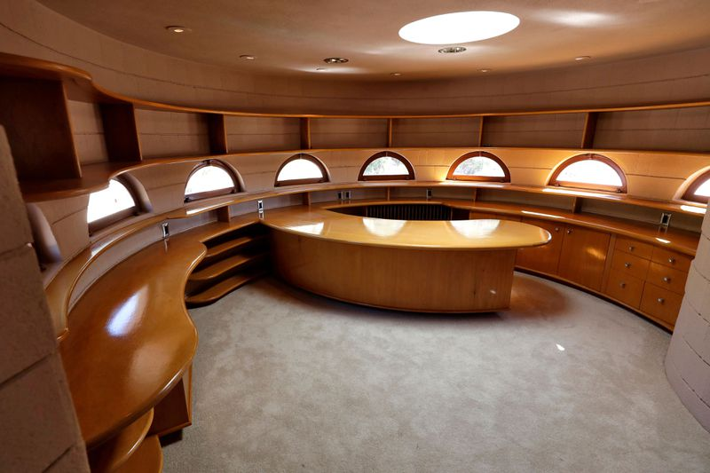 An office with built in desk and wood storage, gray carpets, and windows shaped in half moons.