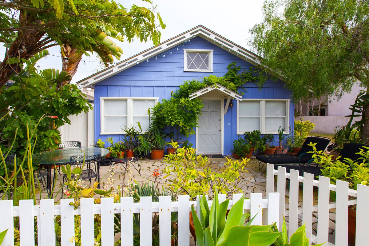 A quaint blue house in Los Angeles, CA with white picket fence, several potted plants, black lounge chairs, and ivy growing along the front.