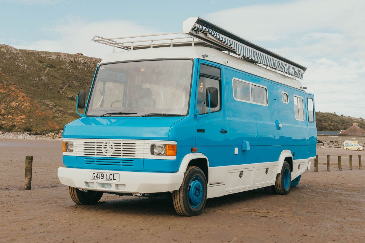 A blue camper van with white trim, large windows, an awning, and a white roof rack. The camper sits on a sandy beach.