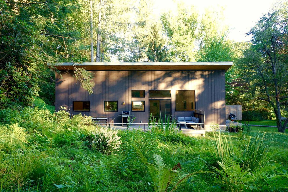 A modern cottage sits in the middle of the woods, with a front porch that has seating and a grill.