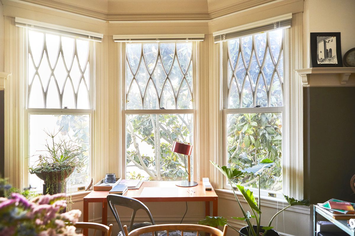 A red desk next to three windows. There are plants in the room.
