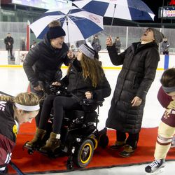 Boston Pride players Marisa Gedman, Denna Laing, and Alex Carpenter drop the puck before Harvard University and Boston College play at Fenway Park in Boston, MA on Jan. 10.