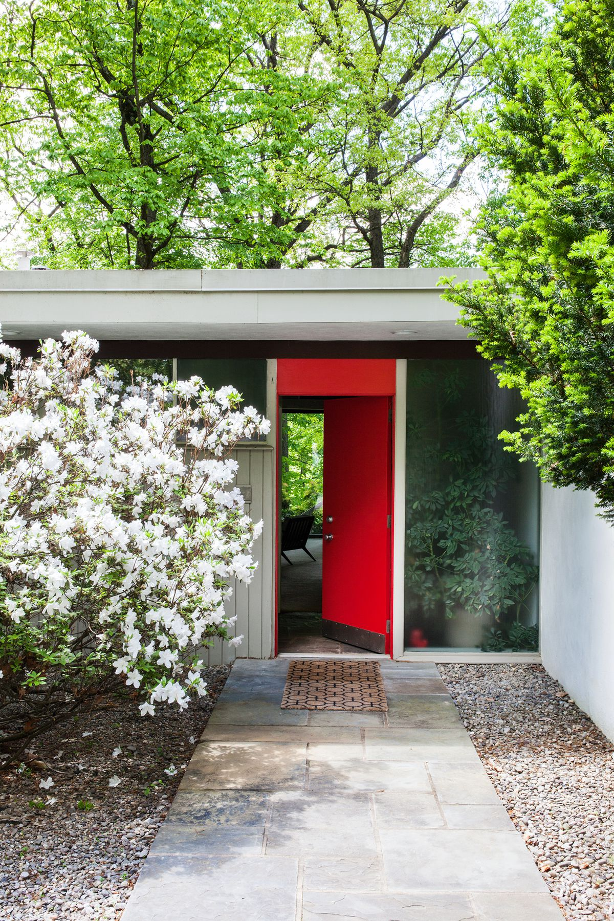 The Neutra house is painted a light gray and has large windows, but the door is painted a bright red.