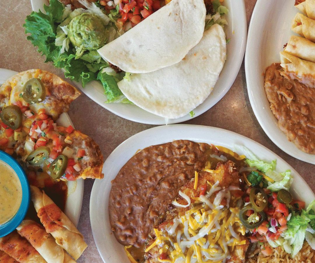 An array of plates, one with tortillas and vegetables, another with a pile of beans and a cheese-covered item.