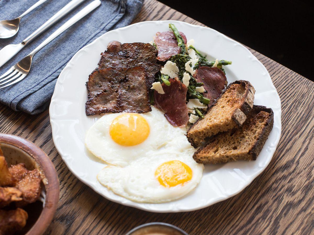 Fried eggs, sautéed greens, sausage, bacon, crispy potatoes, toast on a white plate