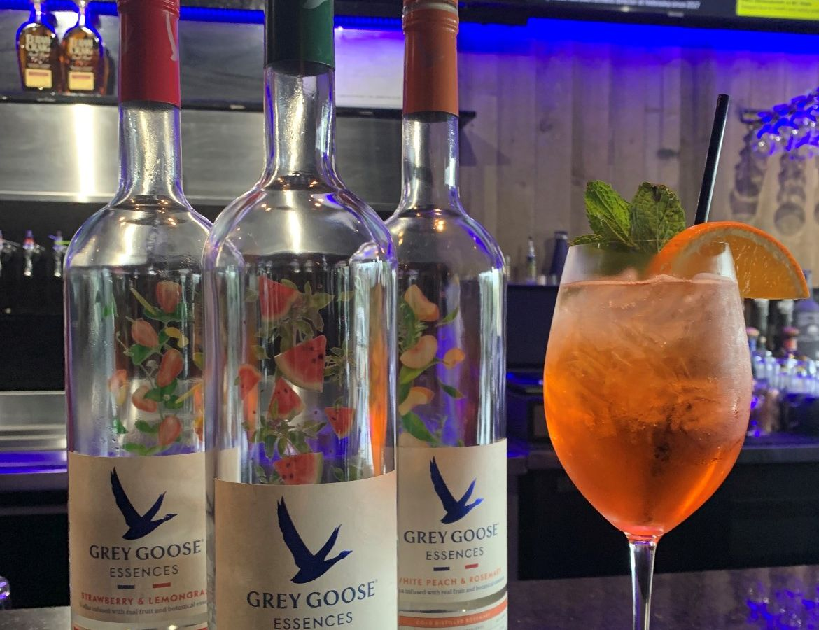 Three Grey Goose Essences liquor bottles on a bar with a spritz drink in a wine glass topped with an orange slice