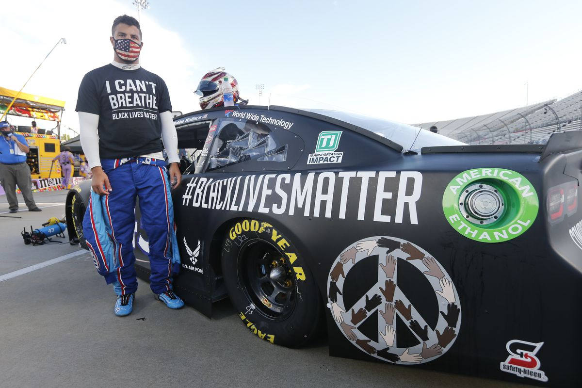 Bubba Wallace stands next to his #BlackLivesMatter car before a race earlier this month.