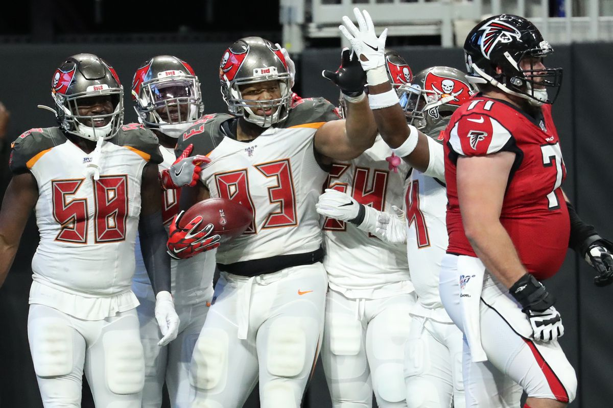 Tampa Bay Buccaneers nose tackle Ndamukong Suh celebrates his fumble returned for a touchdown with safety Mike Edwards and linebacker Shaquil Barrett as Atlanta Falcons offensive guard Wes Schweitzer walks off of the field in the fourth quarter.