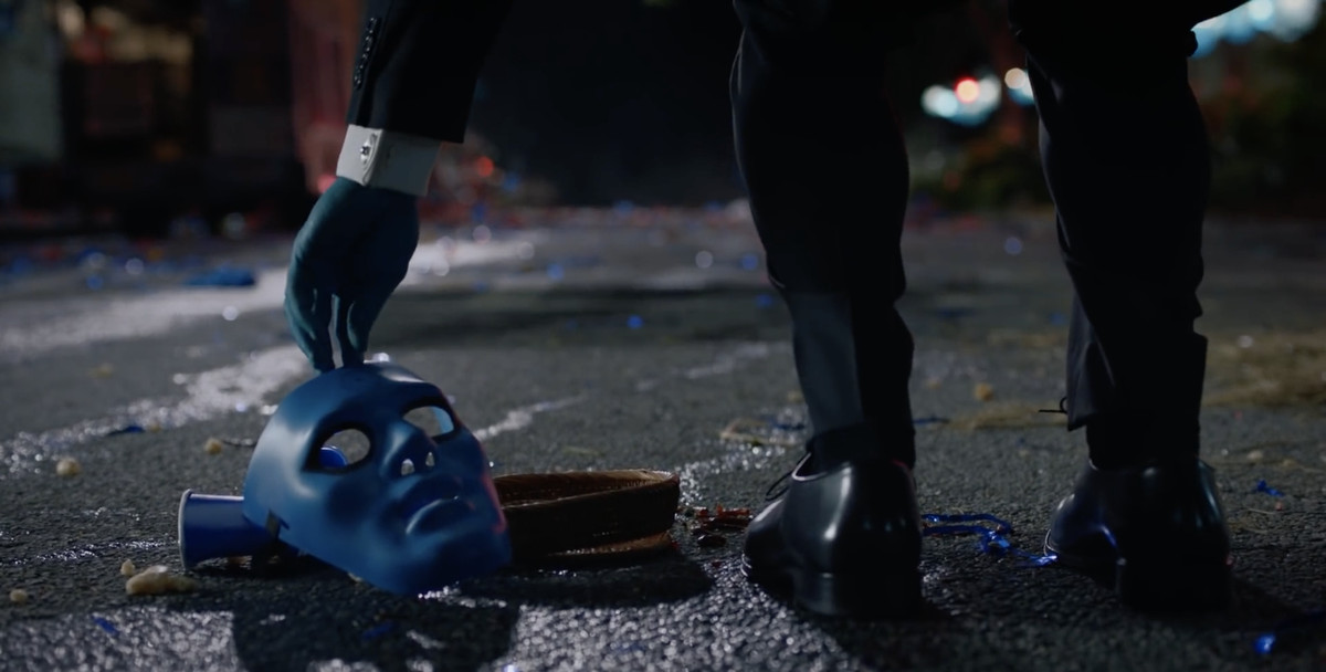 A blue hand reaches down to pick up a Dr. Manhattan mask in the middle of the remnants of a street fair.