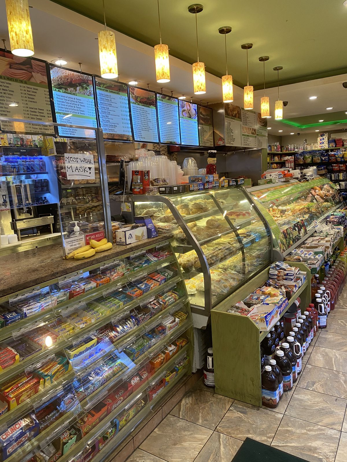 A stocked deli counter with a green ceiling above and yellow lights hanging above the counter