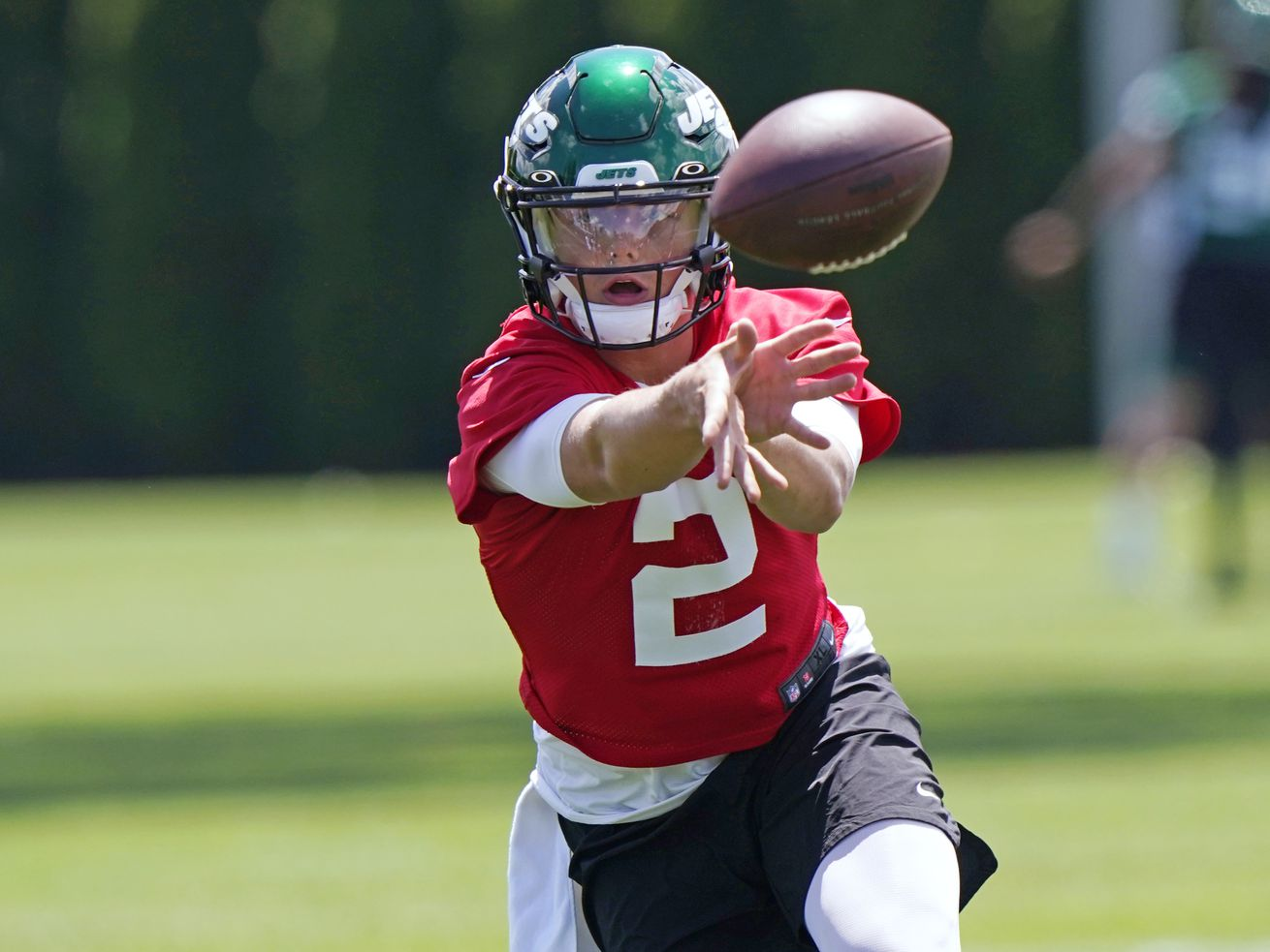 New York Jets quarterback Zach Wilson looks one way while tossing the ball the opposite way during NFL football practice.