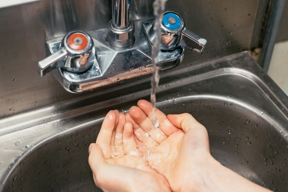 Close up of a person washing their hands in the sink.
