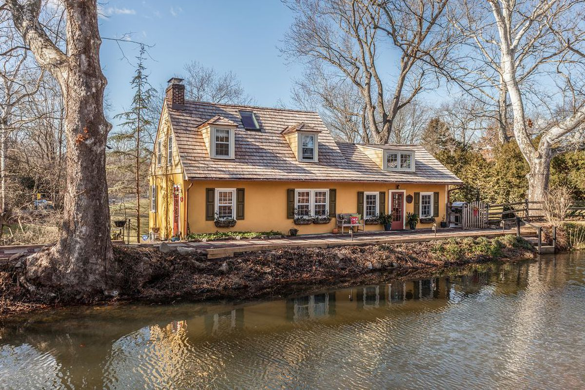 Charming pumpkin-colored cottage sits by a canal with woods in the background.