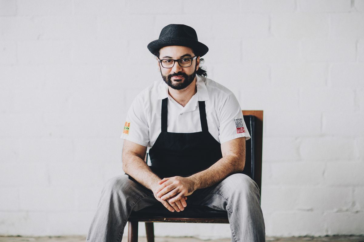 A picture of Wadi sitting on a chair in a white kitchen coat with a black apron over it