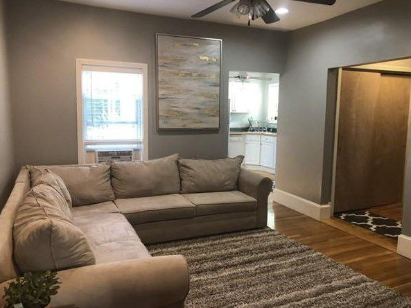 A living room with a sectional couch taking up much of it, and there's a door leading out.