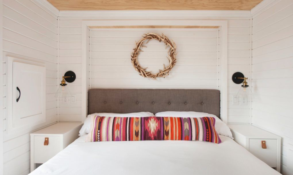 Bed with white comforter and wall sconces
