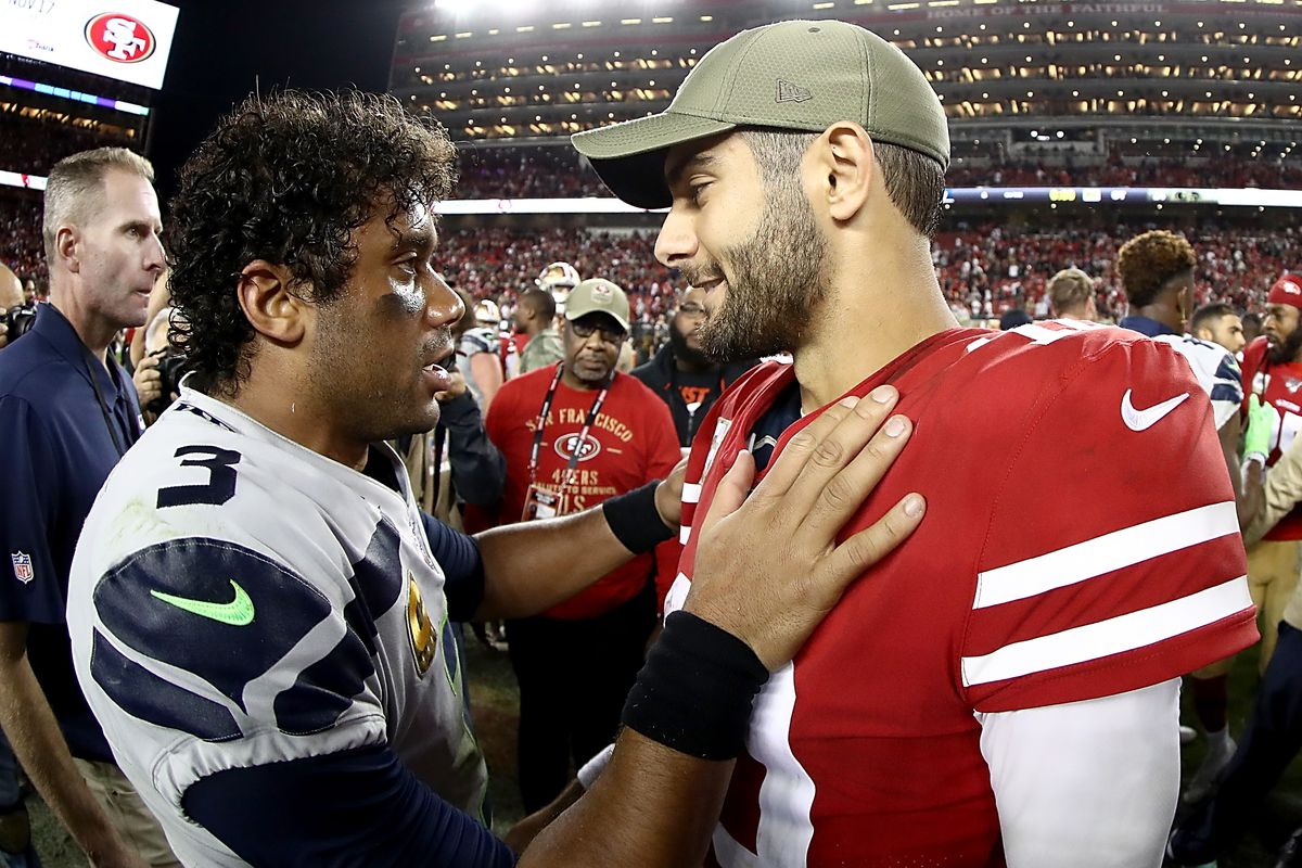 Quarterback Jimmy Garoppolo of the San Francisco 49ers and quarterback Russell Wilson of the Seattle Seahawks talk after the overtime game at Levi's Stadium on November 11, 2019 in Santa Clara, California.