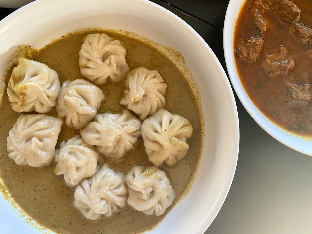 Chicken jhol momos (dumpings in a brown gravy), with a bowl of lamb curry off to the side