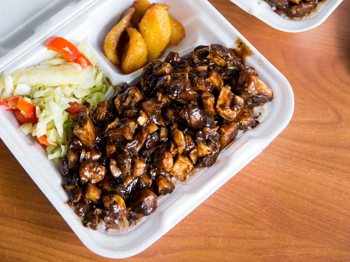 A carryout box filled with curried goat, salad, and plantains.