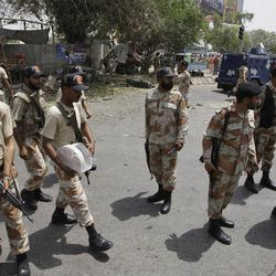 Pakistani security officials secure the area of a suicide attack in Karachi, Pakistan on Thursday, April 5, 2012. Police say a suspected suicide bomber detonated explosives near a vehicle carrying a senior police official in the southern Pakistani city of Karachi, killing scores of people. (AP Photo)