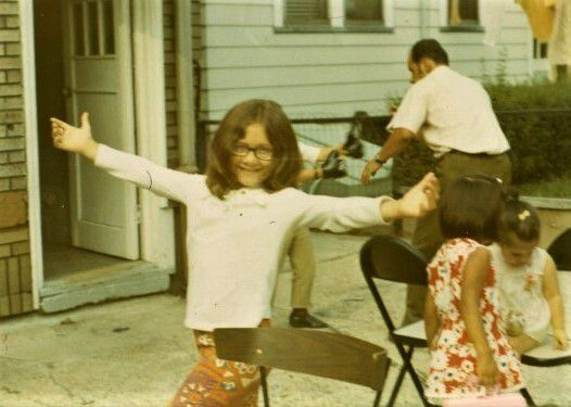 A little girl with glasses, wearing a white blouse and red patterned pants, poses with her arms outstretched with two little girls and a man moving in the background.