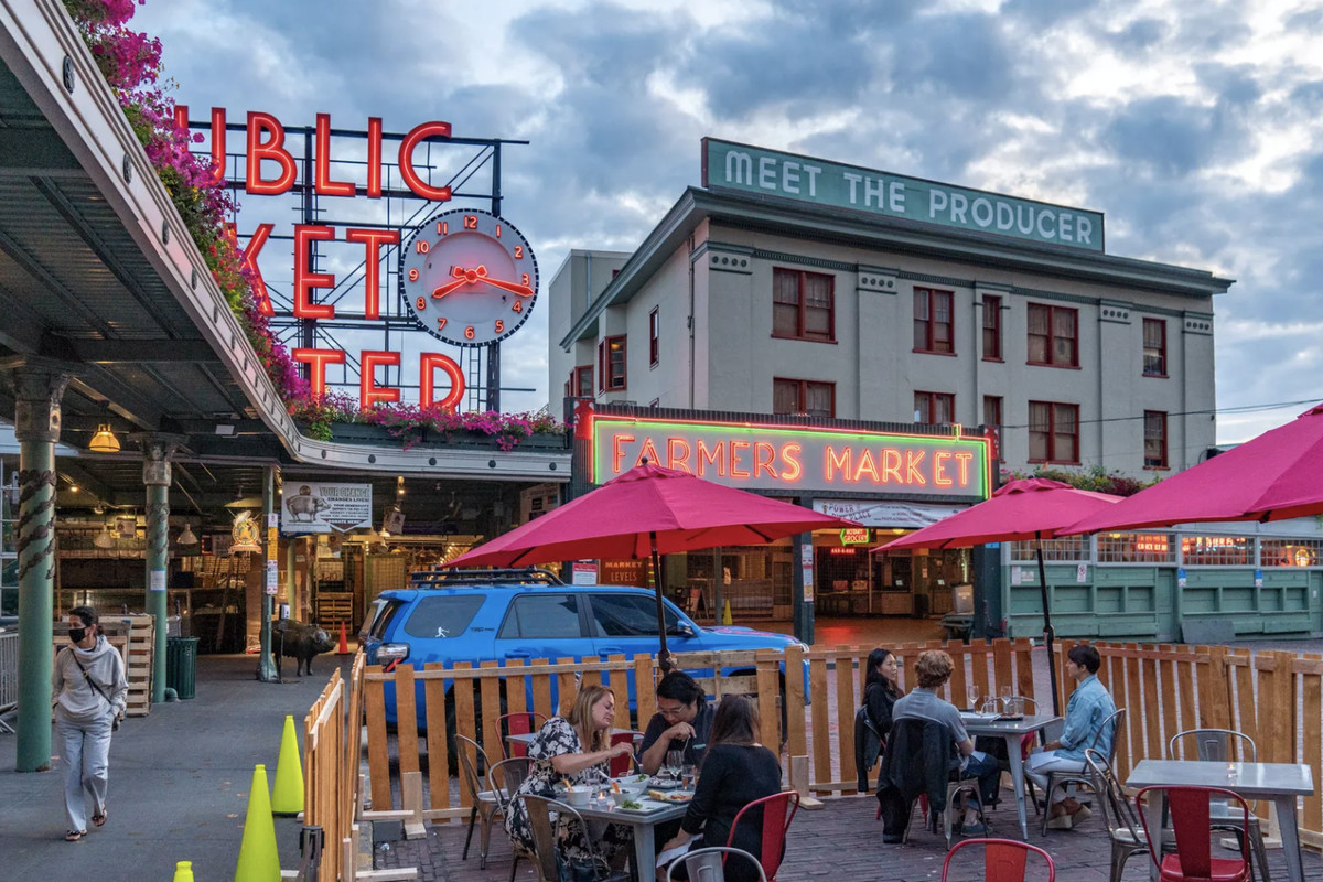 Diners sit in a small outdoor patio across from the iconic Pike Place Market sign covered by pink umbrellas
