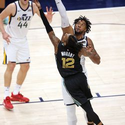 Memphis Grizzlies guard Ja Morant (12) puts in a layup with Utah Jazz center Derrick Favors (15) defending as the Utah Jazz fall to the Memphis Grizzlies play in game one of their NBA playoff series at Vivint Arena in Salt Lake City on Sunday, May 23, 2021. Memphis won 112-109.