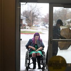 D Stanford folds up an umbrella while assisting his wife, Stacy Davis-Stanford, to class at Salt Lake Community College in Salt Lake City on Thursday, Feb. 27, 2014. Davis-Stanford is in a wheelchair from a debilitating car accident, which caused her to lose her job and thus, her insurance options. She also has other conditions (lupus, kidney disease, neurological issues). She's racked up $200,000 in medical bills and can't afford to get the tests or surgery she needs.