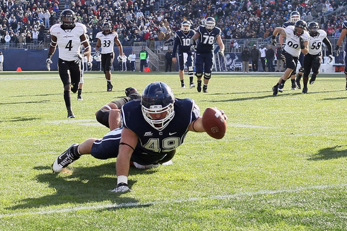 EAST HARTFORD CT:  Anthony Sherman #49 of the Connecticut Huskies scores a touchdown as Wesley Richardson #24 of the Cincinnati Bearcats defends at Rentschler Field in East Hartford Connecticut.  (Photo by Elsa/Getty Images)
