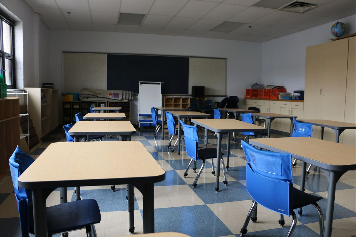 A classroom with blue chairs sits empty.