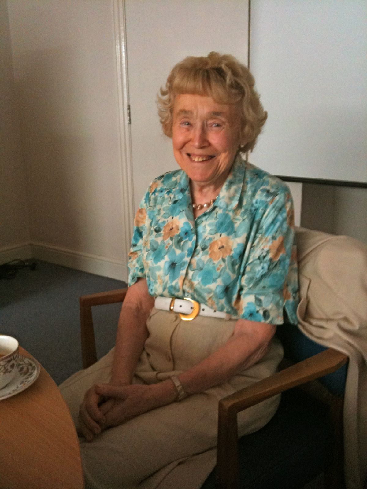 Wing sitting in a chair in a flowery shirt, smiling