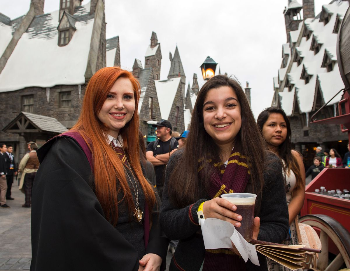 Butterbeer-sipping fans in Hogwarts robes at the Wizarding World of Harry Potter.