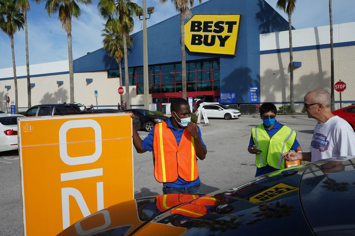 Employees bring a television to a customer's car at a Best Buy store on Black Friday.