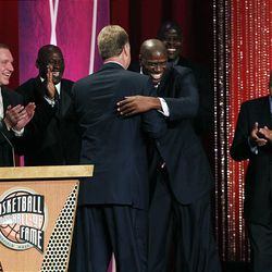 """Basketball Hall of Fame inductees, members of the 1992 U.S. Olympics """"Dream Team,"""" laugh and applaud as Magic Johnson hugs Larry Bird, left, during enshrinement ceremonies in Springfield, Mass., Friday. In back are Chris Mullin, Michael Jordan, Patrick Ewing and coach Lenny Wilkens."""