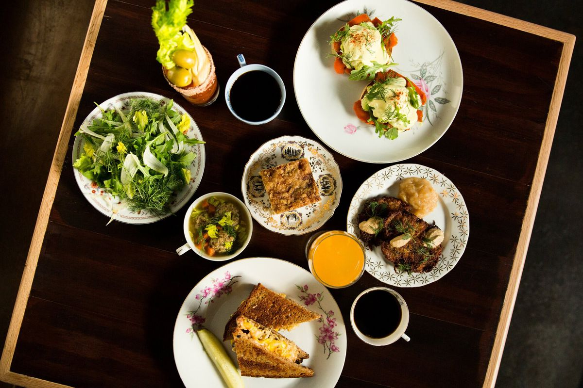 A top-down view of vegan brunch dishes, coffee, and cocktails at Allyum in West Seattle