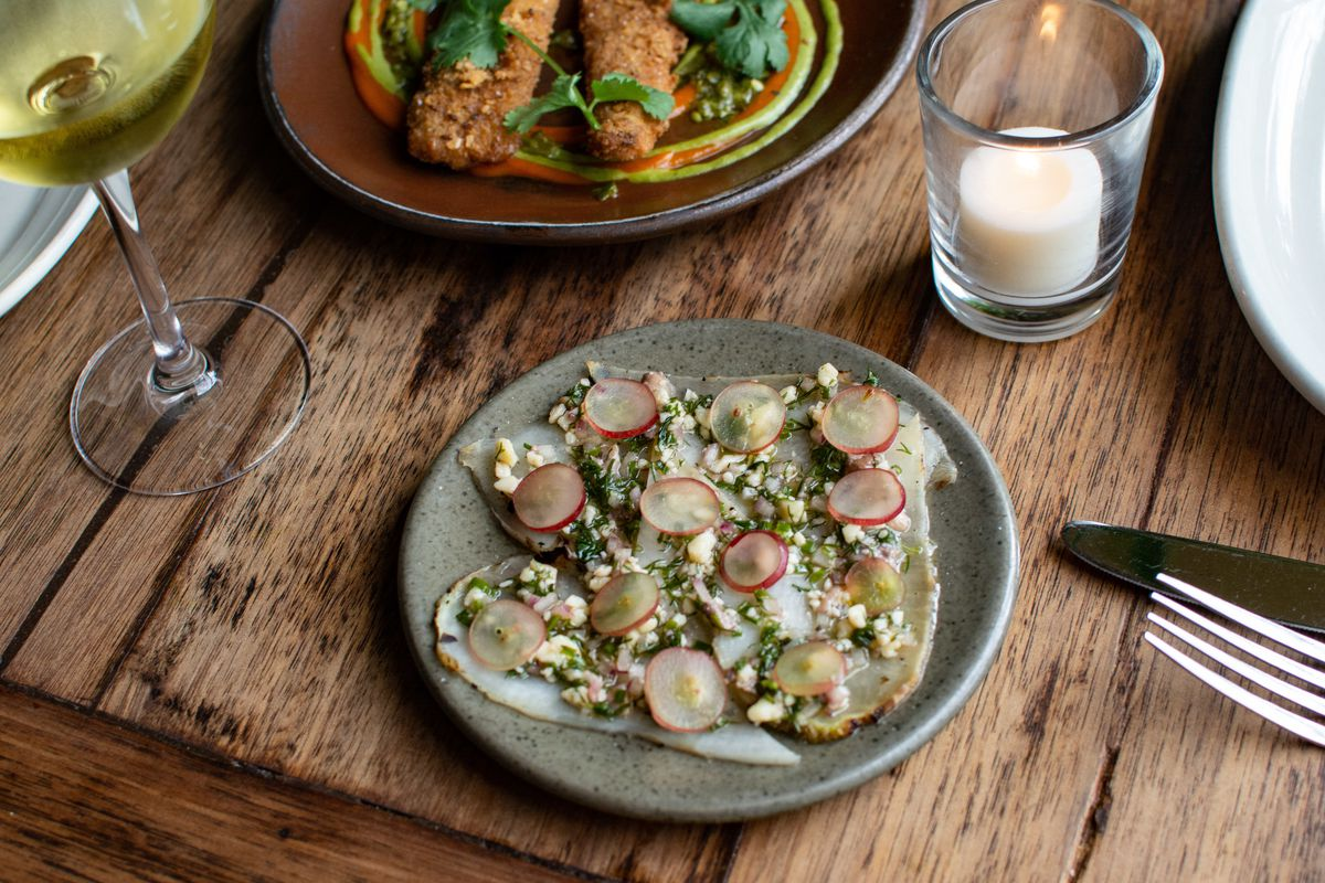 Grilled Radishes with Anchovy, Kashkaval, and Grapes, carrot schnitzel, white wine, on a wood table