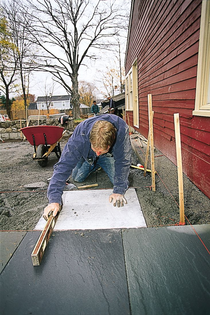 Person laying a DIY patio made of stone.