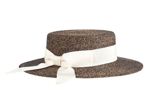 A black and tan straw boater hat with a white ribbon