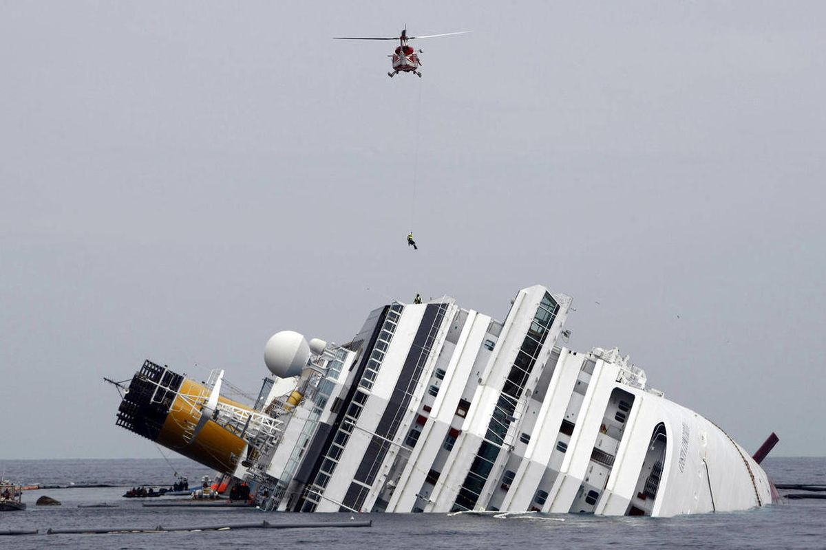 FILE - This Jan. 31, 2012 file photo shows an Italian firefighter being lowered from a helicopter onto the grounded cruise ship Costa Concordia off the Tuscan island of Giglio, Italy. Court-appointed experts have pointed the finger of blame primarily at t