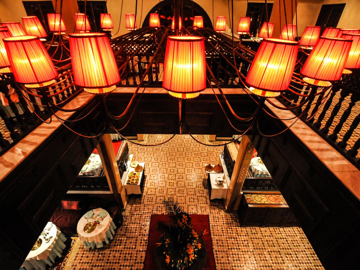 A chandelier with with lamp-like shades suspended over a cut-out in a second-floor walkway, looking down over a dining room below with tiled floor, floral centerpiece, and white tablecloth-lined tables
