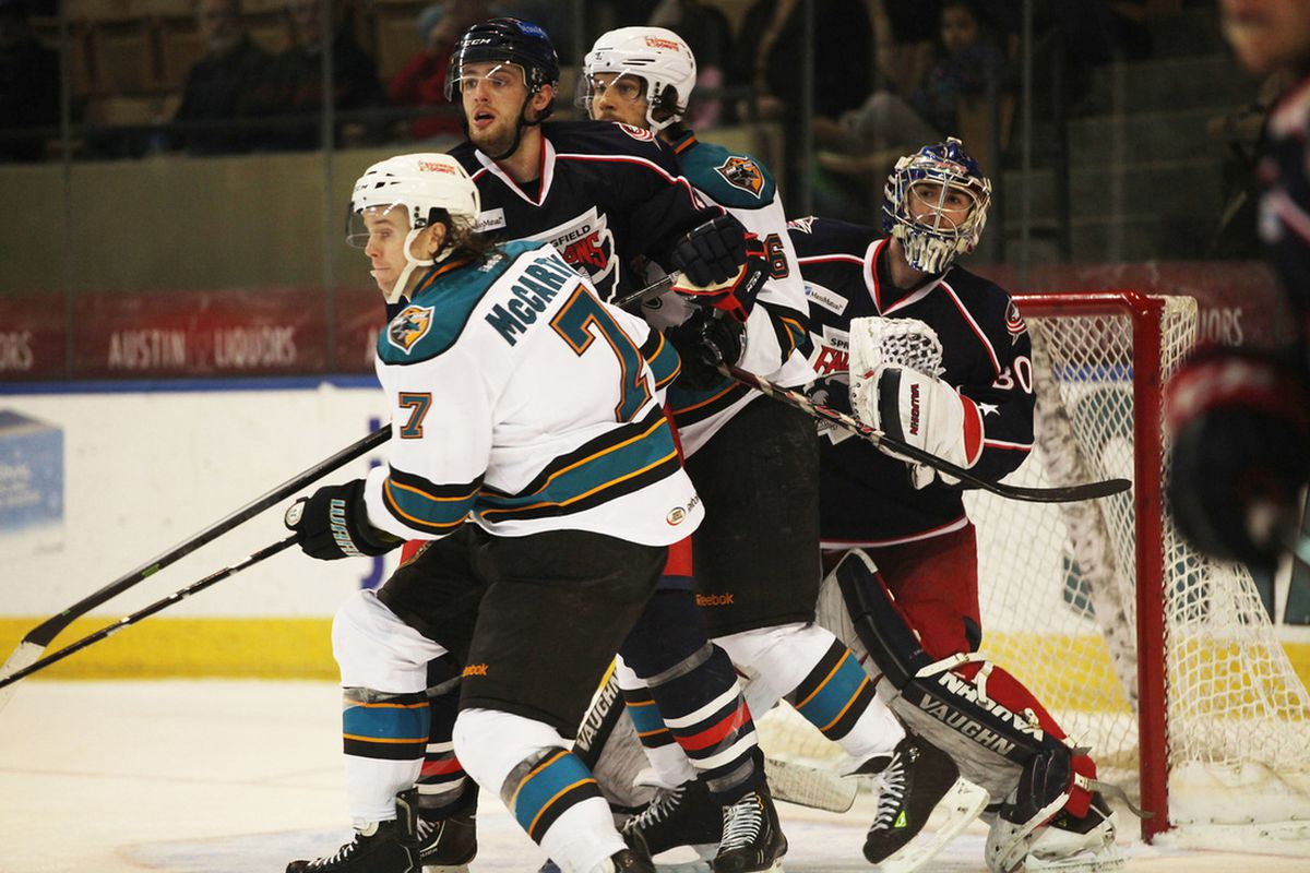 Worcester Sharks forwards John McCarthy and Bracken Kearns battle for positioning in front of Springfield Falcons goaltender Jeremy Smith during Sunday afternoon's game athe DCU Center.