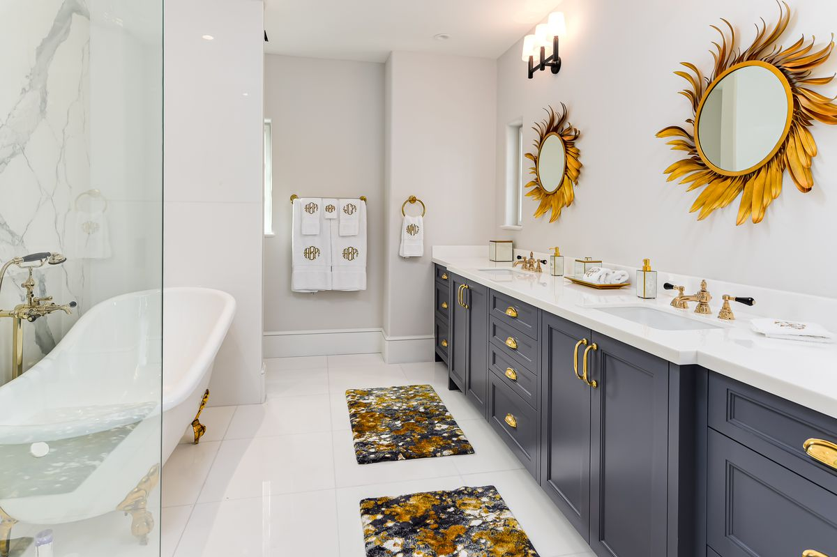 A long bathroom has white countertops, two circle gold mirrors, navy cabinets, and a freestanding white tub.