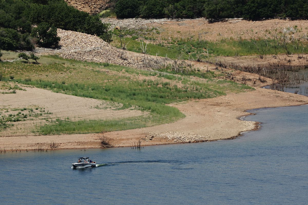 A boater floats at Jordanelle Stake park, where drought has reduced water levels.